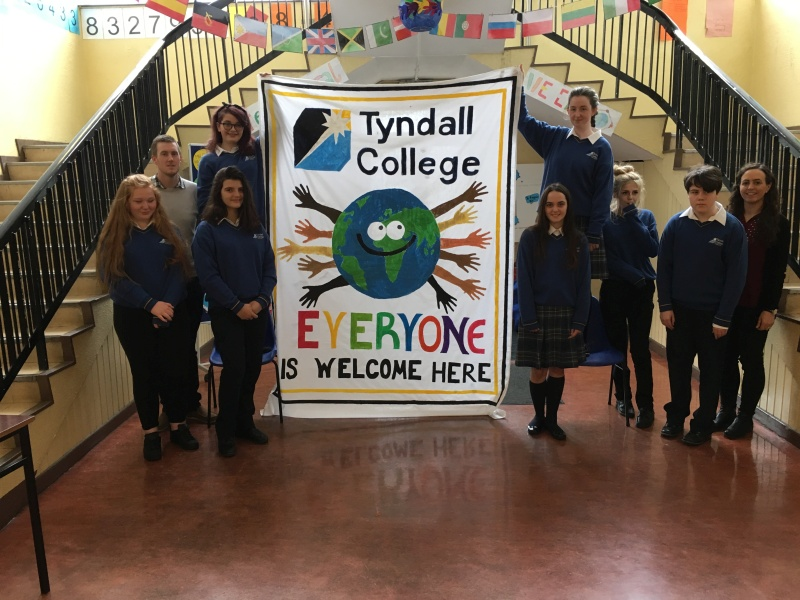 Casey McGrath, Giulia Martinez Perugini, Danielle Harkin Conway, Tracey Doogue, Hope de Faoite-Dickson, Ms Bolger and Mr Doyle unveiling the wonderful Intercultural Week banner they designed and created.